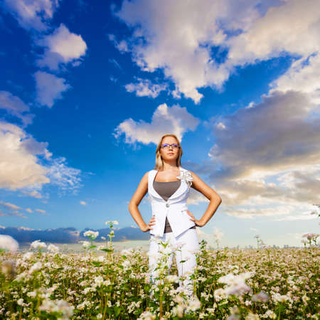 businesswoman standing on flowers field over sunset photo