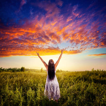 woman stadning on field over sunset under beautiful skies, freedom concept