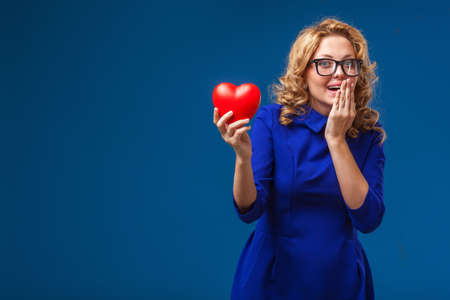 funny blonde woman earing blue dress holding red heart shape over blue  Stock Photo