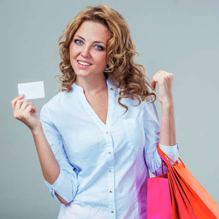 happy blonde woman holding blank card and pepr shopping bags bags, closeup portrait photo