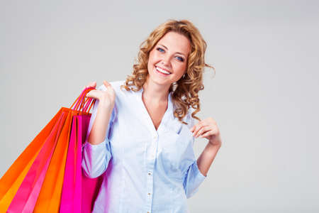 happy blonde woman holding blank card in her pocket, shopping theme photo