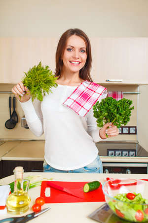 beautiful cheerfu caucasian young woman at home making salad photo