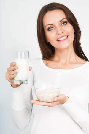 beautiful woman holding glass of mik and bowl with dry oatmeal flakes photo