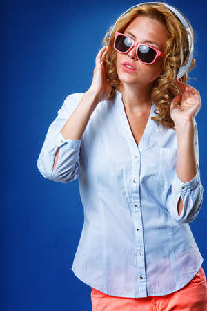 blonde woman wearing white headphones and pink sunglasses photo