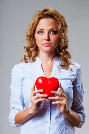 donacion de organos: seriuosly hermosa mujer rubia sosteniendo símbolo rojo del corazón