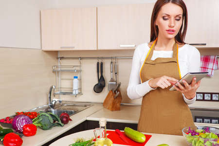 woman using a tablet computer to cook in her kitchen Stock Photo - 26596436