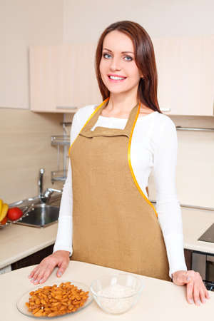 happy young woman at kitchen standing near plate of oatmeal photo
