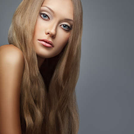 blond hair. Beautiful woman with long hair over gray photo