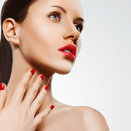 closeup woman portrait with red nails and lips over white, square format photo