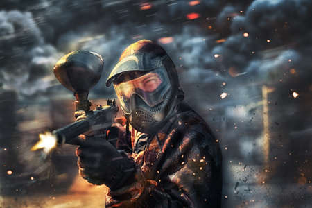 paint gun: paintball sport player wearing protective mask shooting Stock Photo