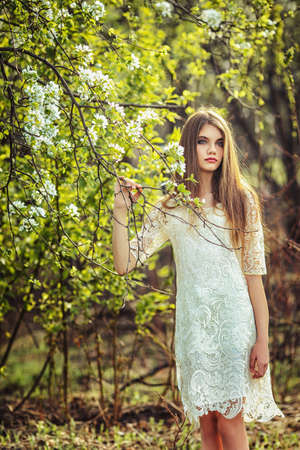 beautiful brunette woman walking outdoors, dramatic theme, spring ground and trees photo