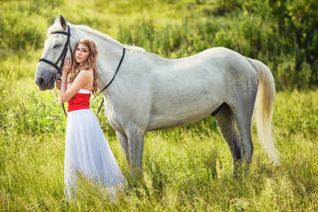 girl in red dress: Beautiful sensual women with white horse wearing white dress Stock Photo