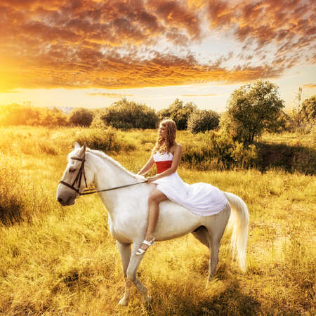 beautiful blonde woman on horse over sunset photo