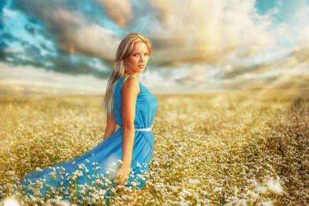 woman wearing blue dress walking on filed photo