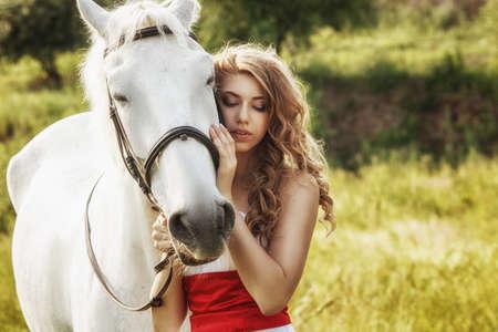 Beautiful women wearing white dress walking outdoors with white horse  photo