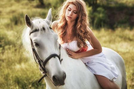 Beautiful women wearing white dress riding on white horse