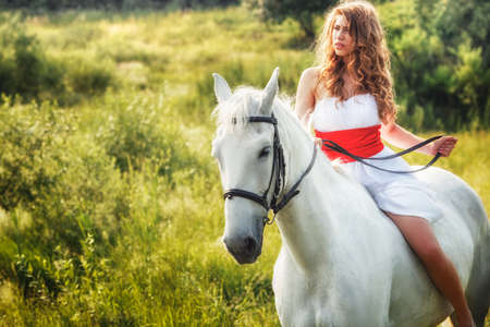 Beautiful women wearing white dress riding on white horse  photo