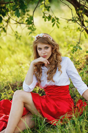 girl in red dress: Romantic portrait of the woman in red skirt sitting under the tree