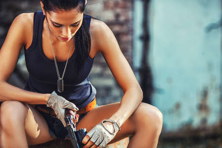 sexy brutal woman sitting in factory ruins and holding handgun 스톡 콘텐츠