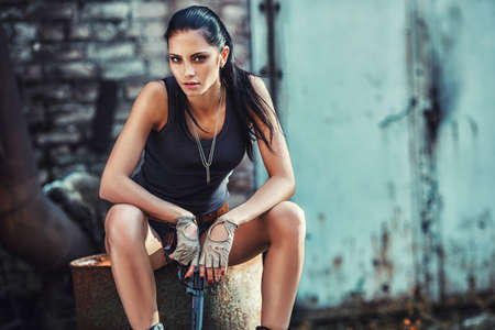 industrial ruins: sexy brutal woman sitting in factory ruins and holding handgun Stock Photo