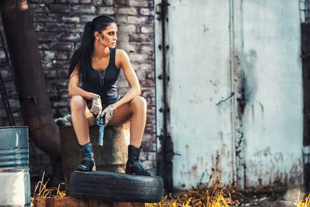 sexy brutal woman sitting in factory ruins and holding handgun Stock Photo