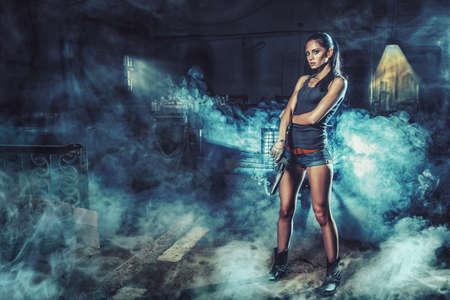 mujer con pistola: Mujer brutal sexy de pie sobre las ruinas de la fábrica y la celebración de arma de fuego
