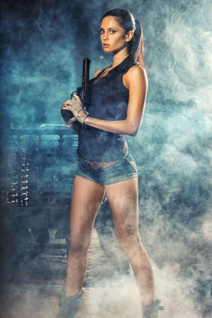 sexy brutal woman standing on factory ruins and holding handgun