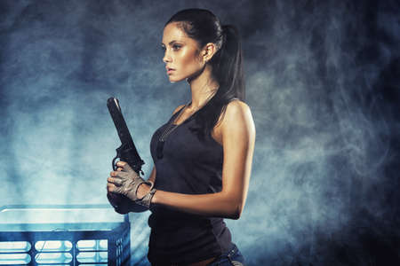 sexy brutal woman standing on factory ruins and holding handgun photo