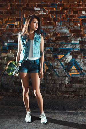 board shorts: Beautiful asian teen girl with skate board. Outdoors, urban lifestyle.