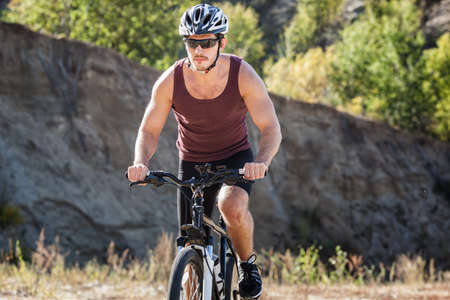 persevere: athlete man cycling on a bicycle ounddors in stone pit
