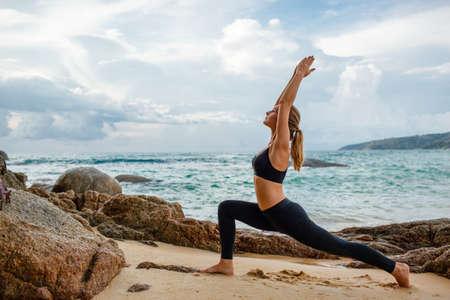 Blonde junge Frau macht Yoga mit dem Ozean hinter Standard-Bild - 34502281