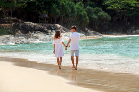 strolling: Vacation couple walking on beach together in love holding hands each other Stock Photo