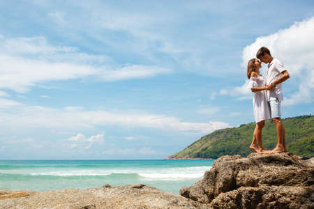 lovely couple: lovely young adult couple standing on the rocks above tropical sea Stock Photo