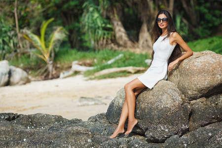 nue plage: belle femme bronzée portant robe blanche assis sur la pierre