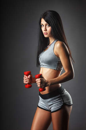 Sports beautiful young woman with red dumbbells photo