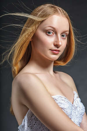flying hair: closeup studio portrait of woman with flying hair