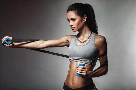 brunett atletisk kvinna träna med gummitejp Stockfoto