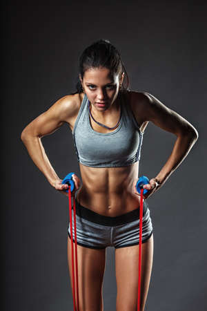 athletic wear: brunette athletic woman exercising with rubber tape