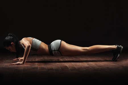 culturista: hermosa mujer atlética empujado desde el suelo