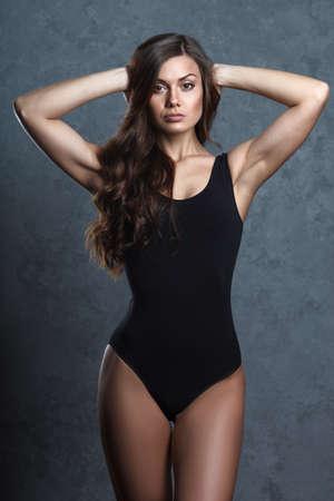 turnanzug: schöne Frau im schwarzen Anzug posiert auf grauem Hintergrund