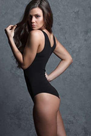 leotard: beautiful woman in black leotard posing on grey background