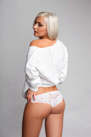 nude female buttocks: Sensual portrait of sexy blonde woman in sweater and panties over light gray background