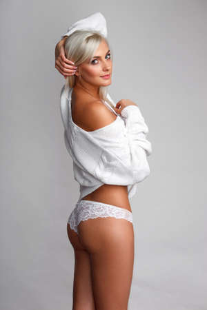 naked sexy girl: Sensual portrait of sexy blonde woman in sweater and panties over light gray background