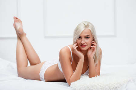 nude blond: Beautiful sexy blonde woman in white lingerie lying on bed Stock Photo