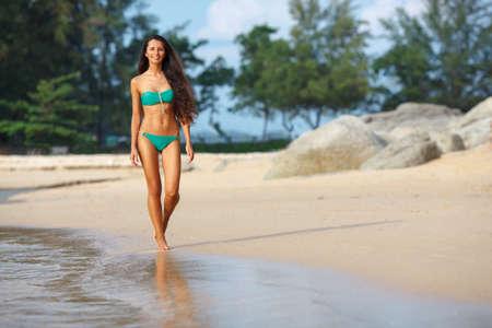 slender woman: tanned beautiful brunette walking along the tropical beach