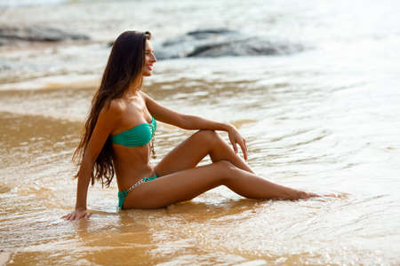 faraway: tanned beautiful brunette sitting on tropical beach looking faraway