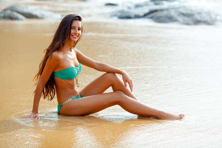 tanned beautiful brunette sitting on tropical beach photo