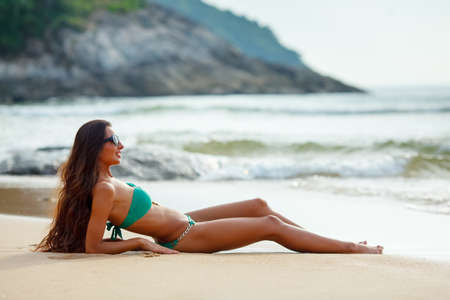 long legs: tanned beautiful brunette laying on tropical beach