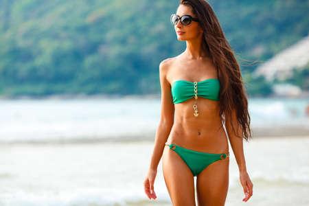niñas en bikini: bronceada hermosa morena caminando por la playa tropical