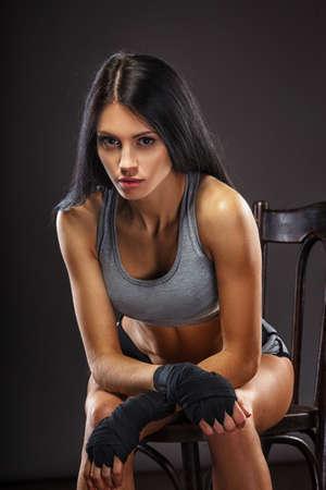 pelo castaño claro: preciosa morena mujer boxeador sentado en silla sobre fondo oscuro